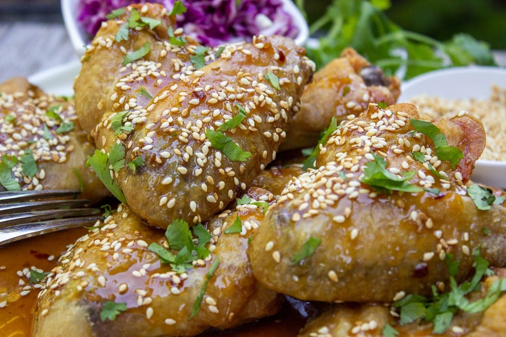 close up of baked chicken wings with honey garlic sauce garnished with sesame seeds on plate 2
