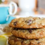 3 Skor chocolate chip cookies stacked on saucer in front of teacup p