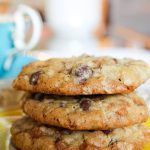 3 Skor chocolate chip cookies stacked on saucer in front of teacup p1