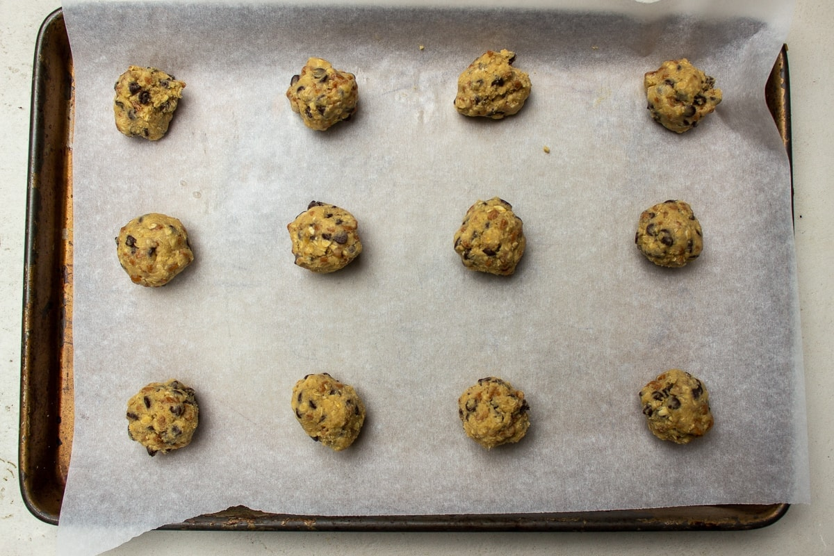 one inch balls of doughon parchment paper on pan