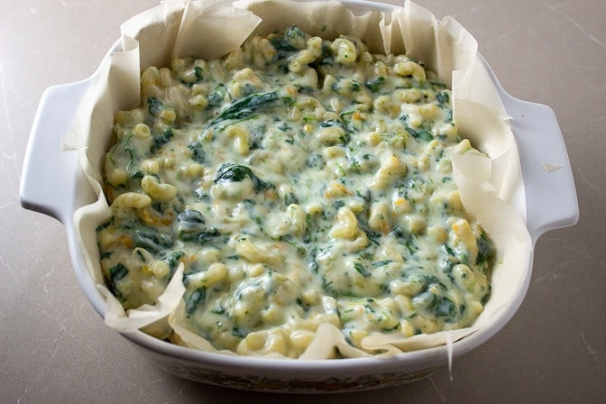 Spinach Mac and Cheese in casserole lined with parchment