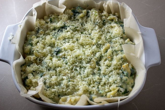 Spinach Mac and Cheese topped with extra cheese in casserole lined with parchment
