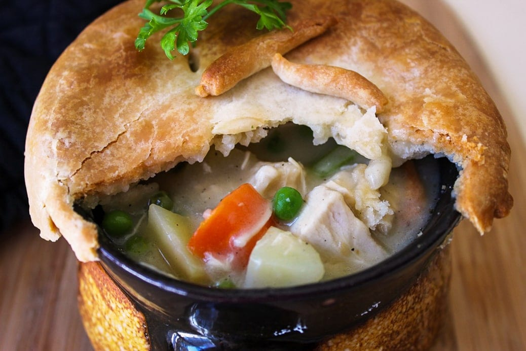 Individual Chicken Pot Pies with part of crust cut open peering inside