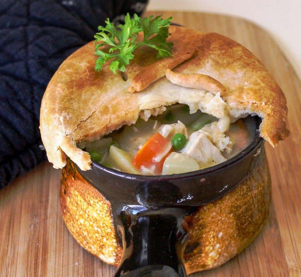 Individual Chicken Pot Pies with part of crust cut open peering inside sitting on cutting board