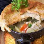 individual chicken pot pie partially cut open to see chicken vegetables and gravy inside p