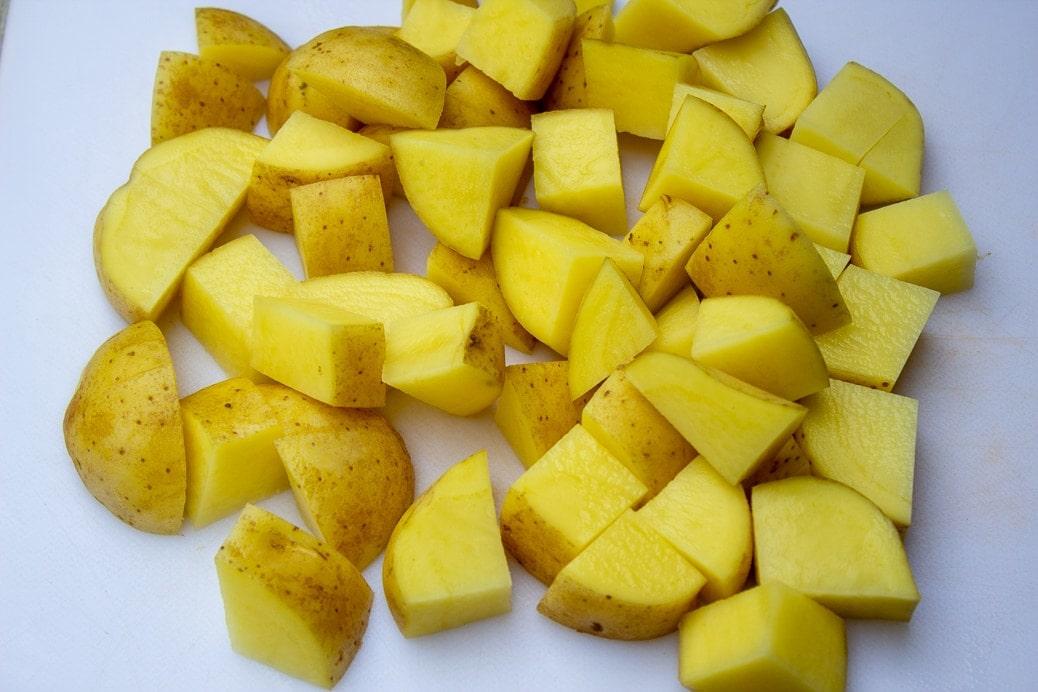 potatoes on cutting board cut into chunks