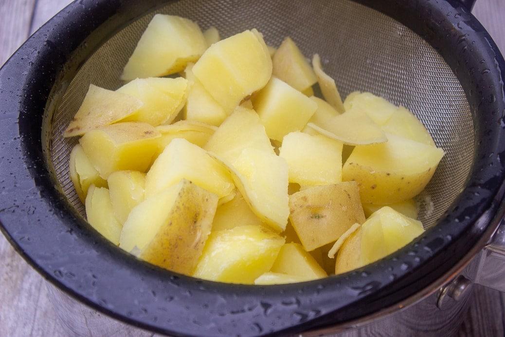 boiled potatoes draining in sieve