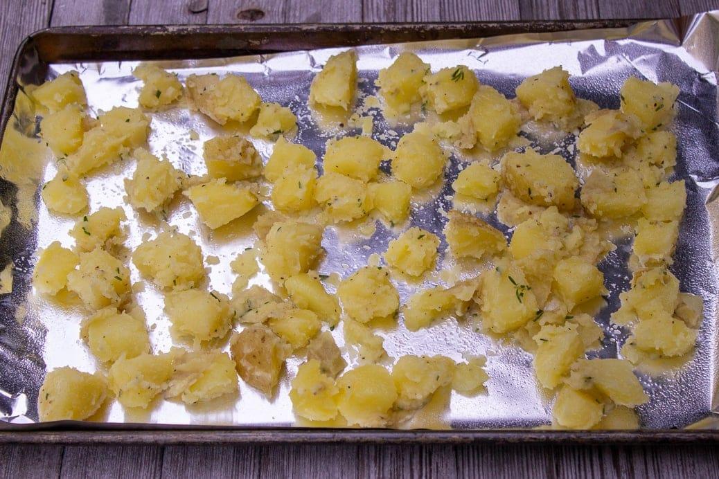 seasoned boiled potatoes in single layer on pan