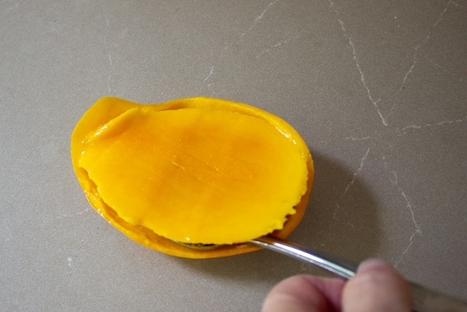 scooping flesh of mango from skin with spoon