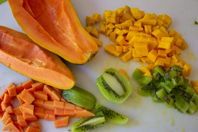 mango kiwi papaya cut open and partially diced cutting board