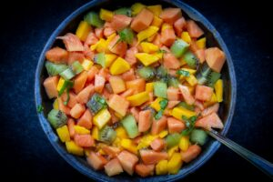 Fruit Salad with kiwi manago papaya and orange juice in bowl