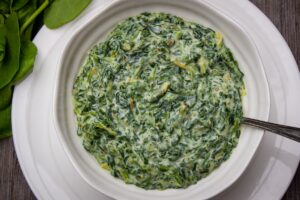 Creamed Spinach in a serving bowl sitting on a plate f