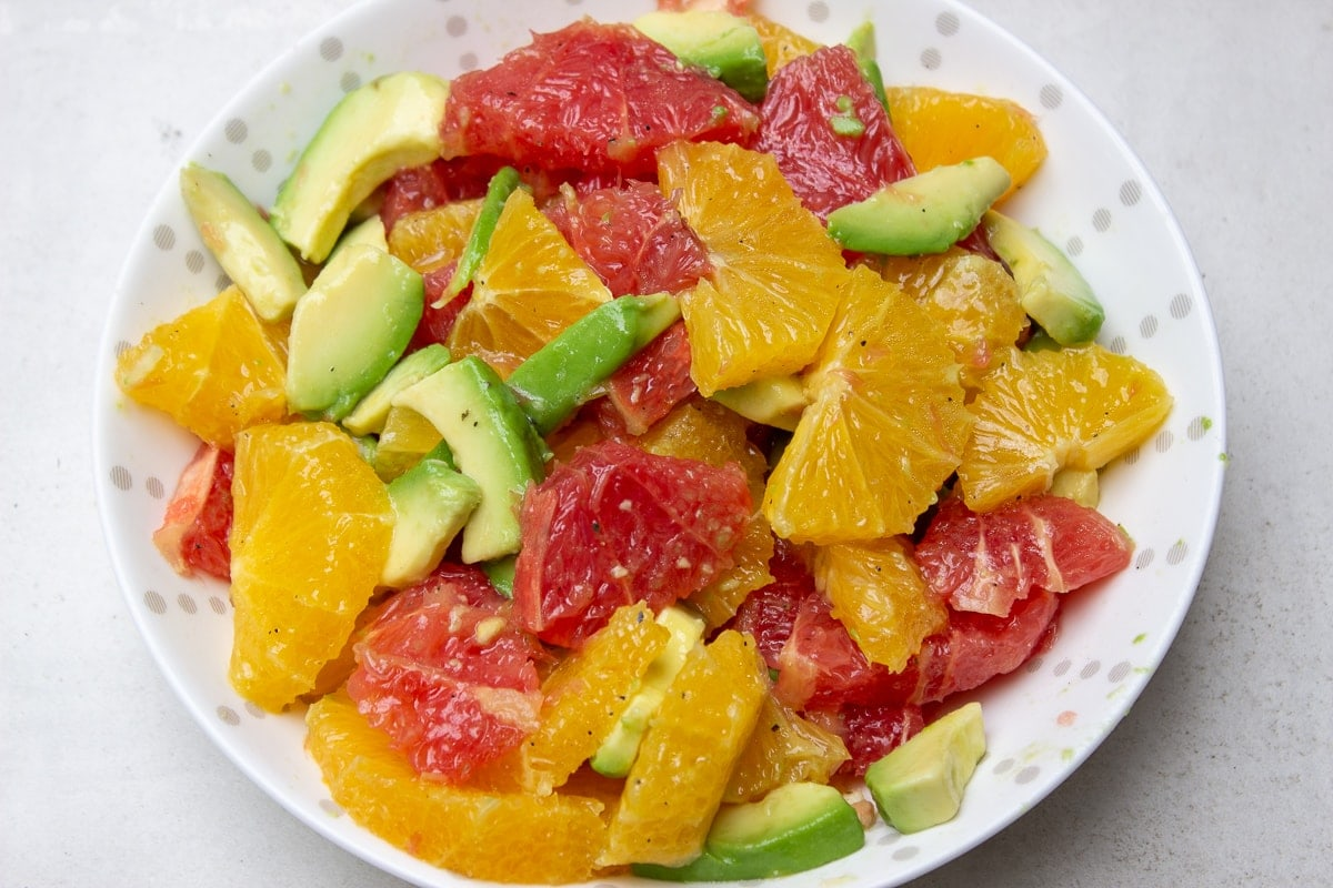 fruit and avocado in bowl with dressing