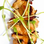 skewer of peanut chicken garnished with pea shoots