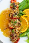 chicken skewer on plate with oranges p