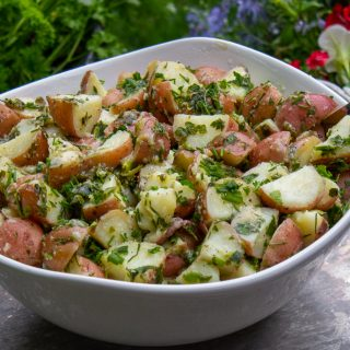 Herb Potato Salad in bowl on tray in garden