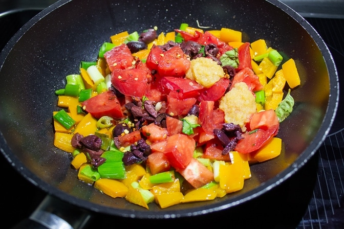 tomatoes, green onions, spinach, basil, olive oil salt, garlic, chili flakes, olives in saute pan