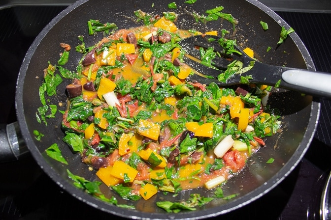 tomatoes, green onions, spinach, basil, olive oil salt, garlic, chili flakes, olives in saute pan with fresh chopped spinach and basil added