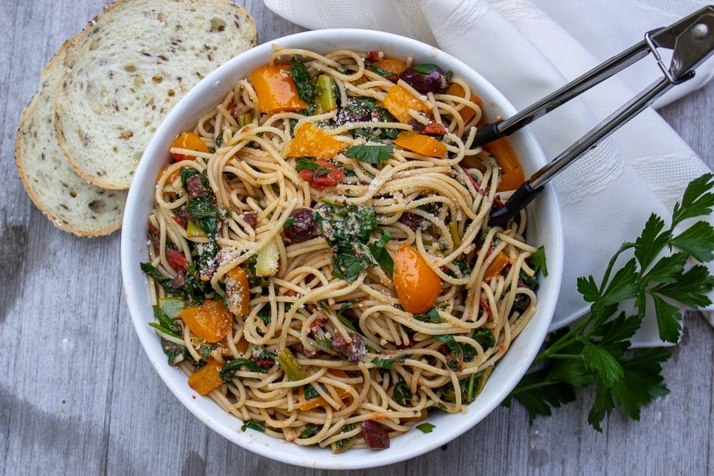 Mediterranean Pasta in serving bowl on table with bread
