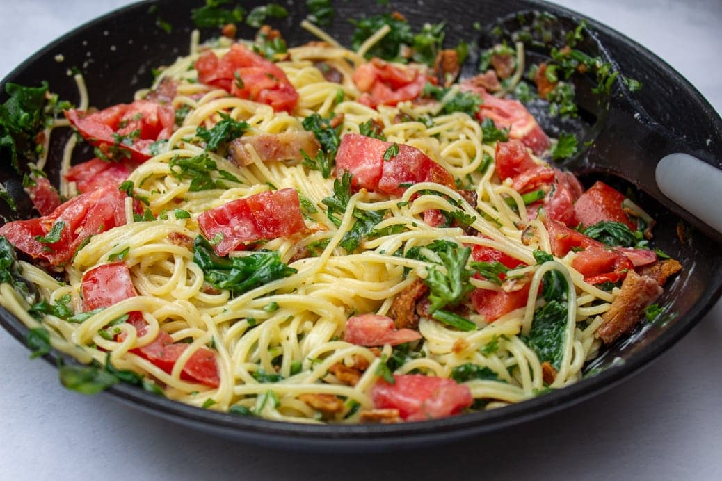 spaghetti carbonara with tomatoes and spinach in pan