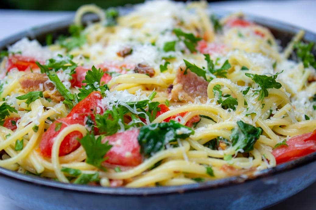spaghetti carbonara with tomatoes and spinach in bowl 1