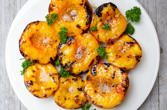 grilled peach halves on a plate f