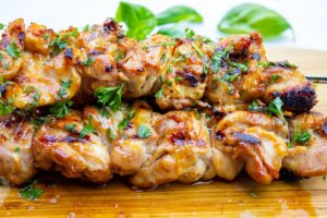 3 grilled chicken skewers on a cutting board f