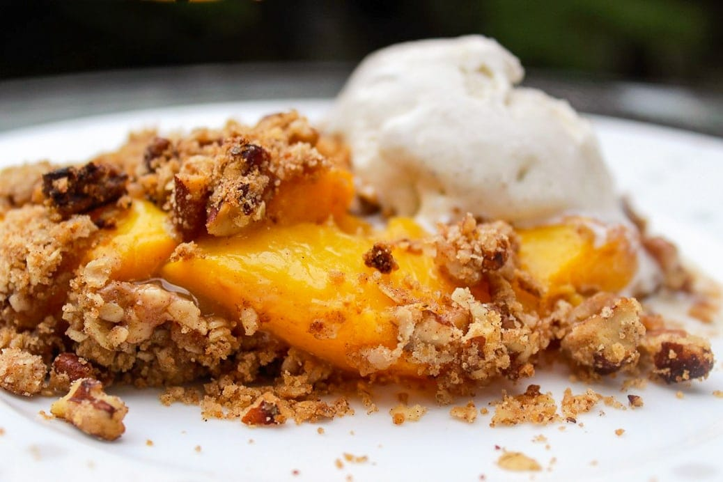 Peach Crumble on a plate with vanilla ice cream