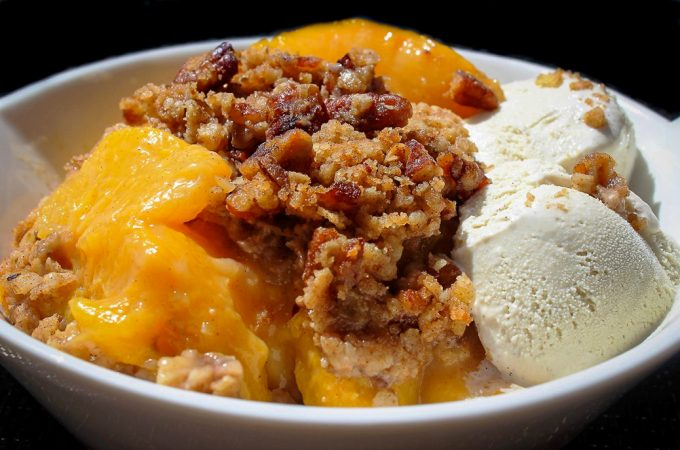 Peach Crumble in a bowl with vanilla ice cream