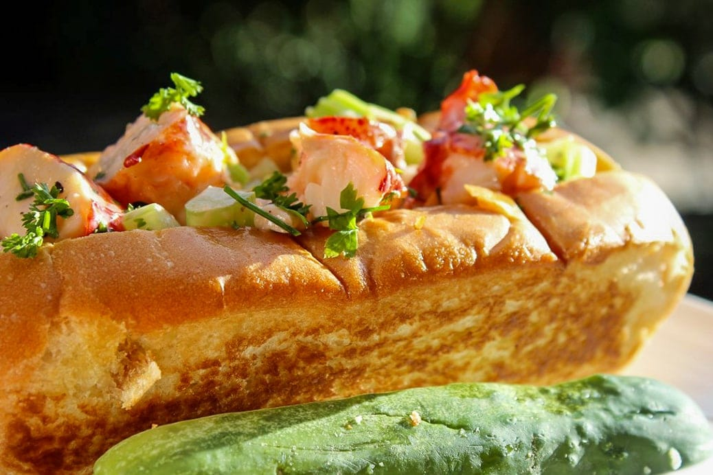 lobster rolls in a toasted butter hot dog bun with a pickle