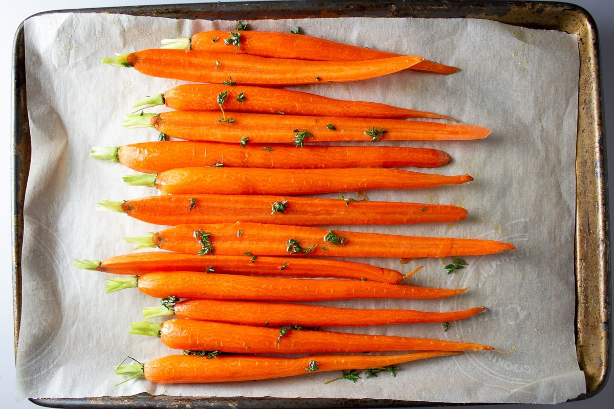 raw carrots on pan with honey mixture and thyme