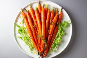 Roasted Honey-Thyme glazed Carrots on a plate garnished with orange zest and thyme