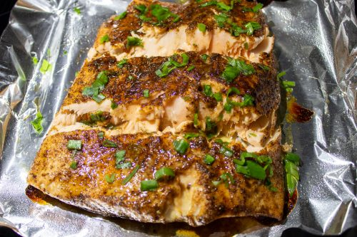 Sweet and Spicy Salmon cut in 3 pieces on pan after roasting, garnished with green onions