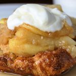 apple french toast casserole on plate with dollop of sour cream on top