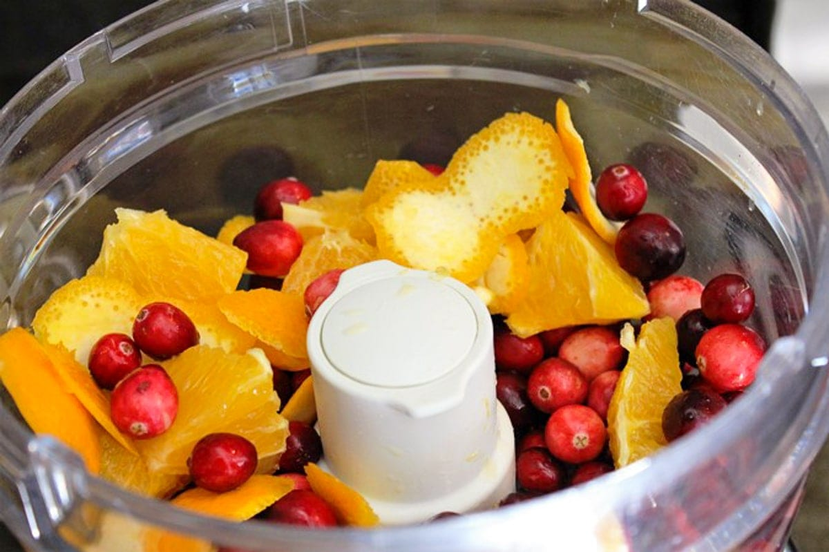 orange, cranberry and sugar in food processor bowl