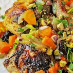 company chicken with ctirus sauce smothered in carrots, onions, prunes and pistachios