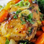 piece roasted citrus chicken on plate with carrots prunes and pistachios