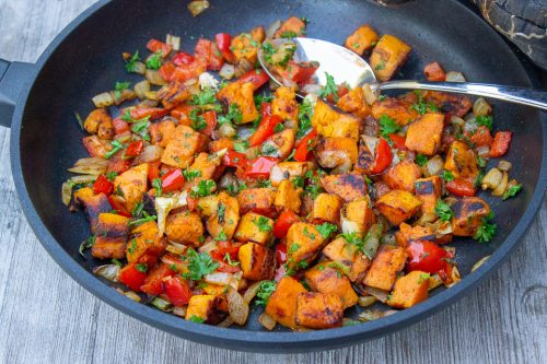 Vegetarian Sweet Potato Hash in a pan sitting on wooden board
