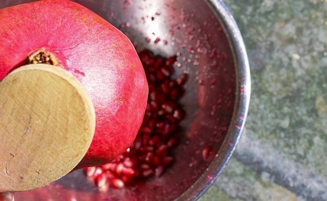 hitting pomegranates over a bowl to extract seeds