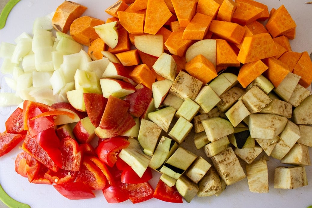 cut up sweet potatoes, apple, pepper, eggplant, onion on cutting board
