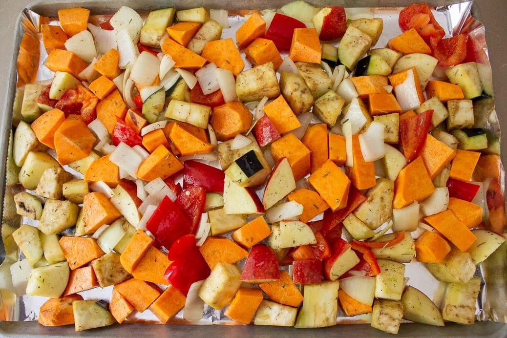 veggies with oil and seasonings in sheet pan