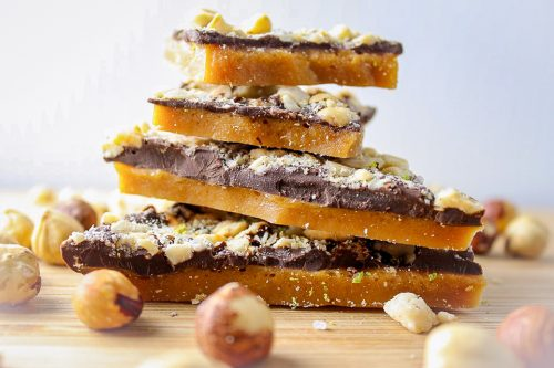 Chocolate toffee stacked on board with hazelnuts