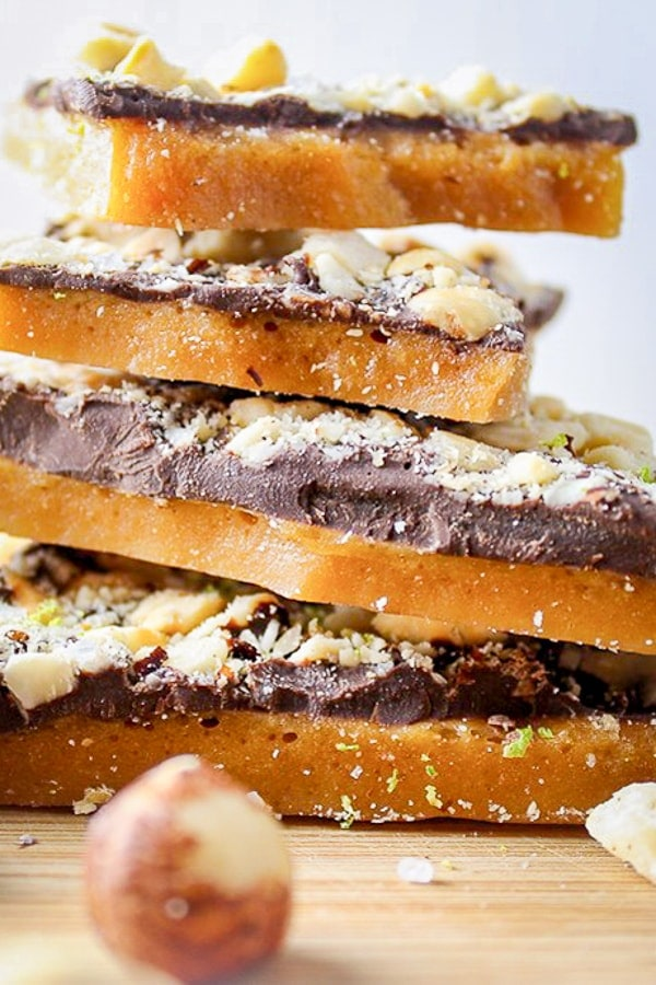 4 pieces chocolate toffee with hazelnuts stacked on plate with whole hazelnuts