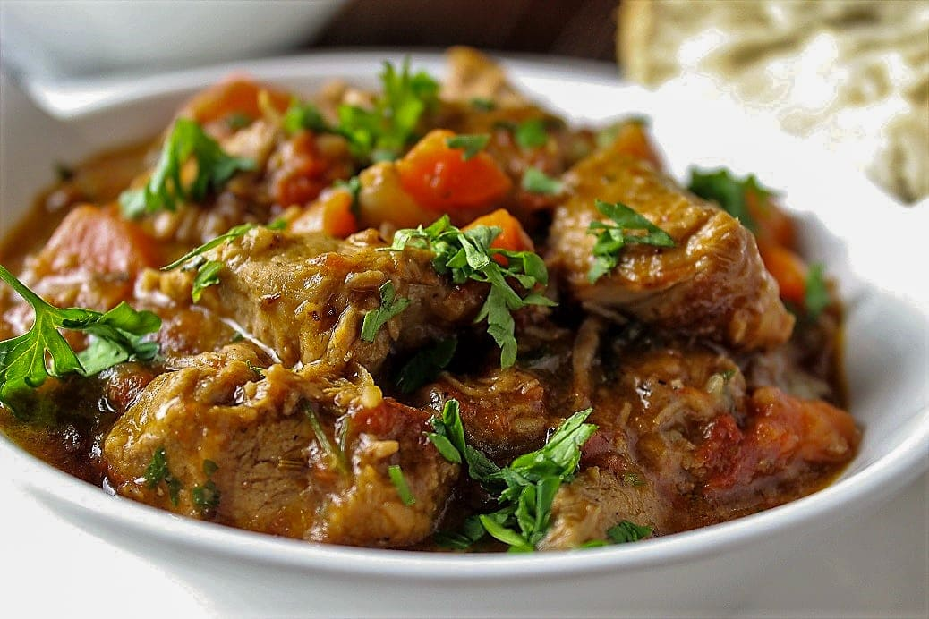 veal stew in a bowl sprinkled with parsley