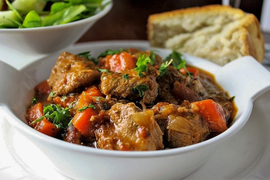veal stew in a bowl with bread and salad on side