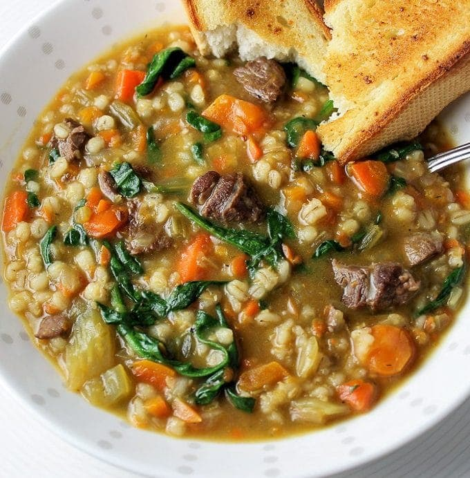 beef barley vegetable soup in a bowl with toasted bread for dipping