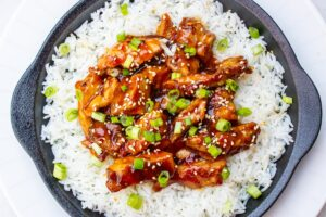 bourbon chicken over rice on plate f