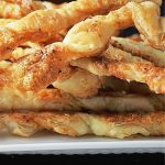 pile of baked flaky cheese twists on plate (close up) p