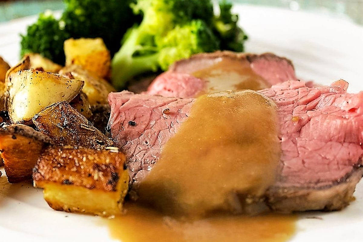 slices of prime rib with gravy and potatoes and broccoli on plate