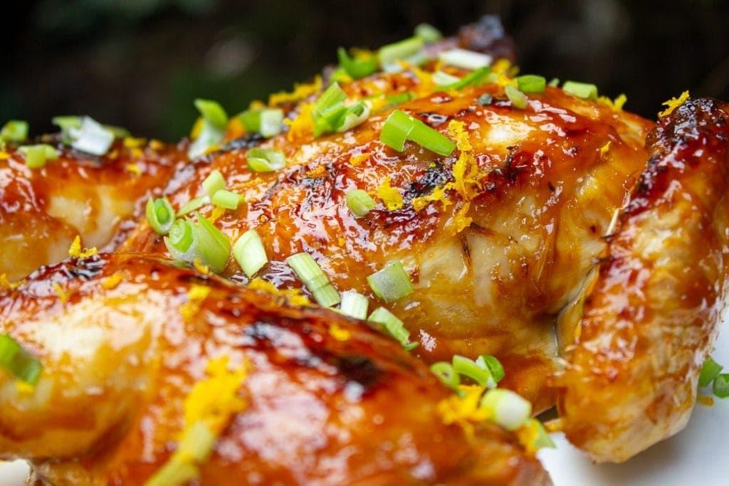Spatchcock Roast Chicken glazed with orange teriyaki sauce on platter